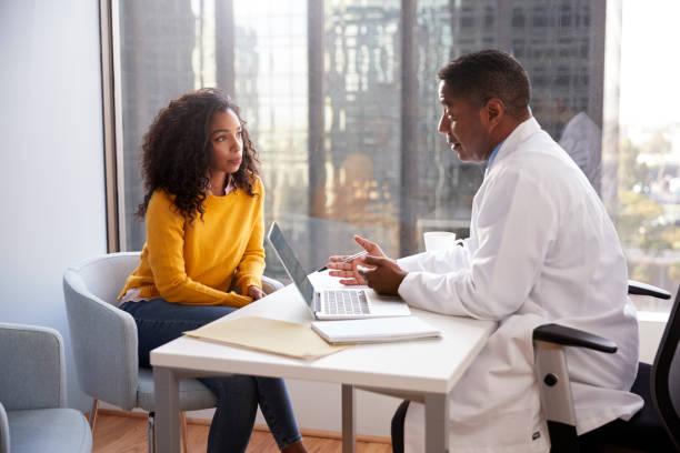在醫院辦公室與男醫生求診的嚴重婦女 - doctor patient 個照片及圖片檔