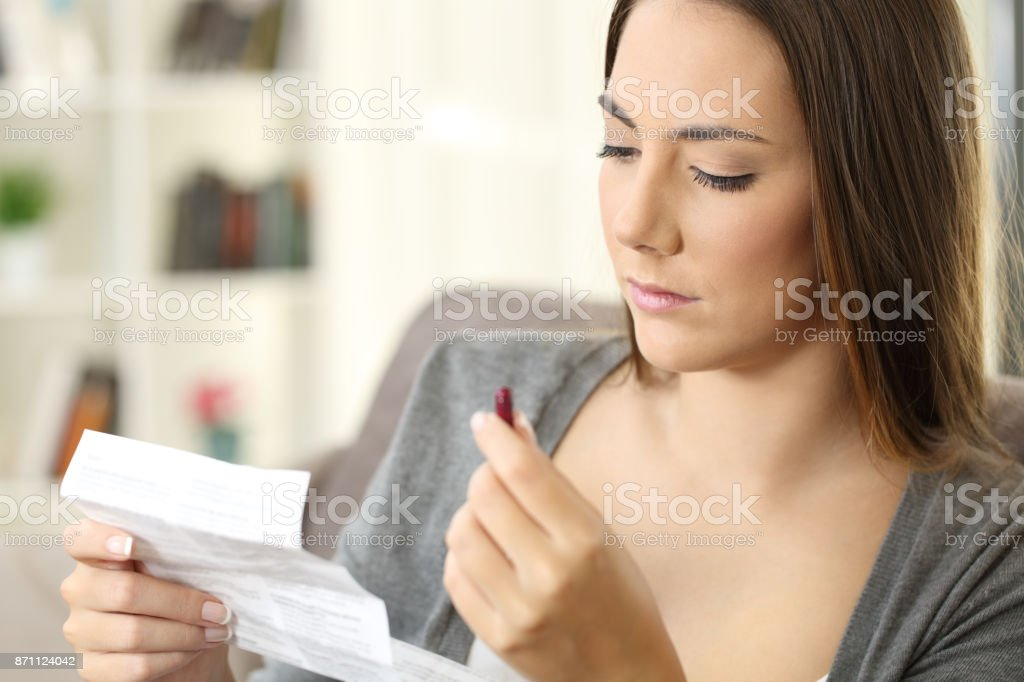 Serious woman holding a medicine reading a leaflet stock photo