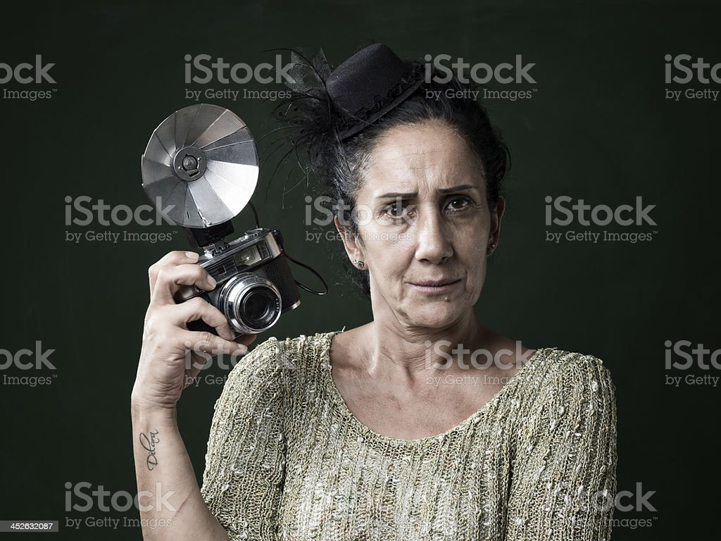 Serious woman holding old fashioned camera stock photo