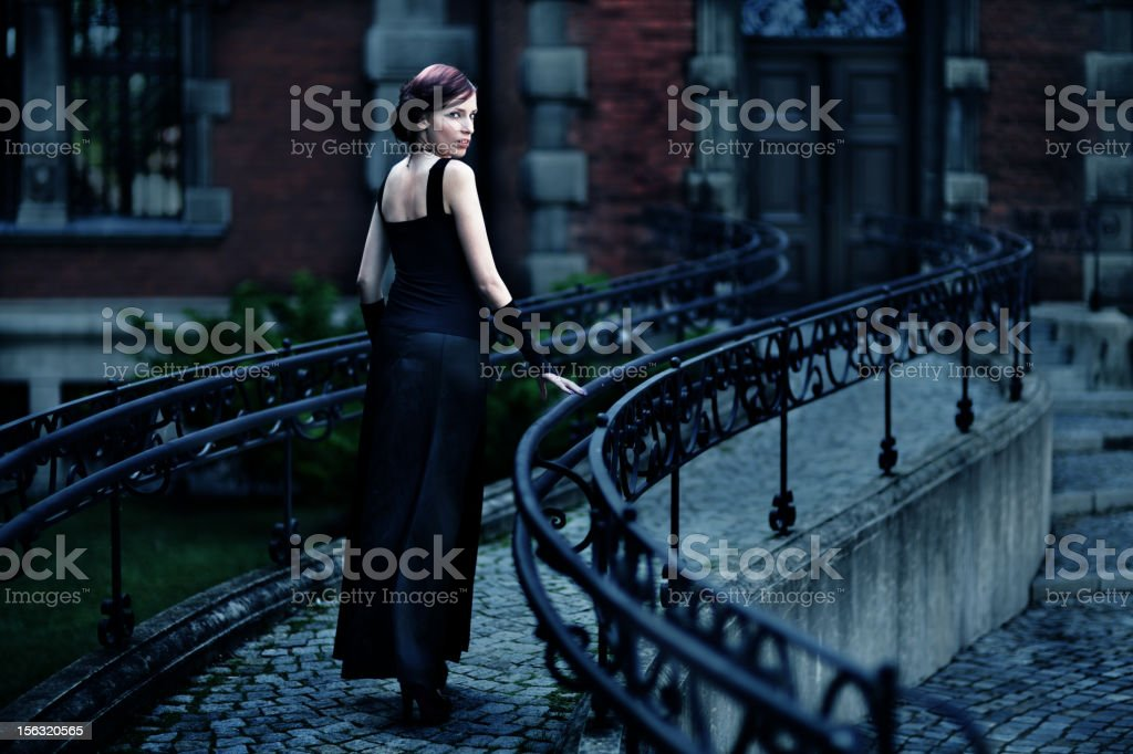 Serious woman in black dress stock photo