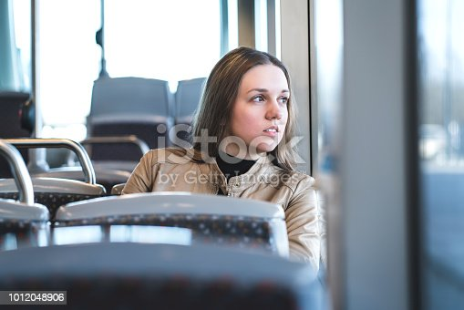 Serious woman in train or bus looking through the window. Thoughtful passenger in public transportation. Upset lady traveling.