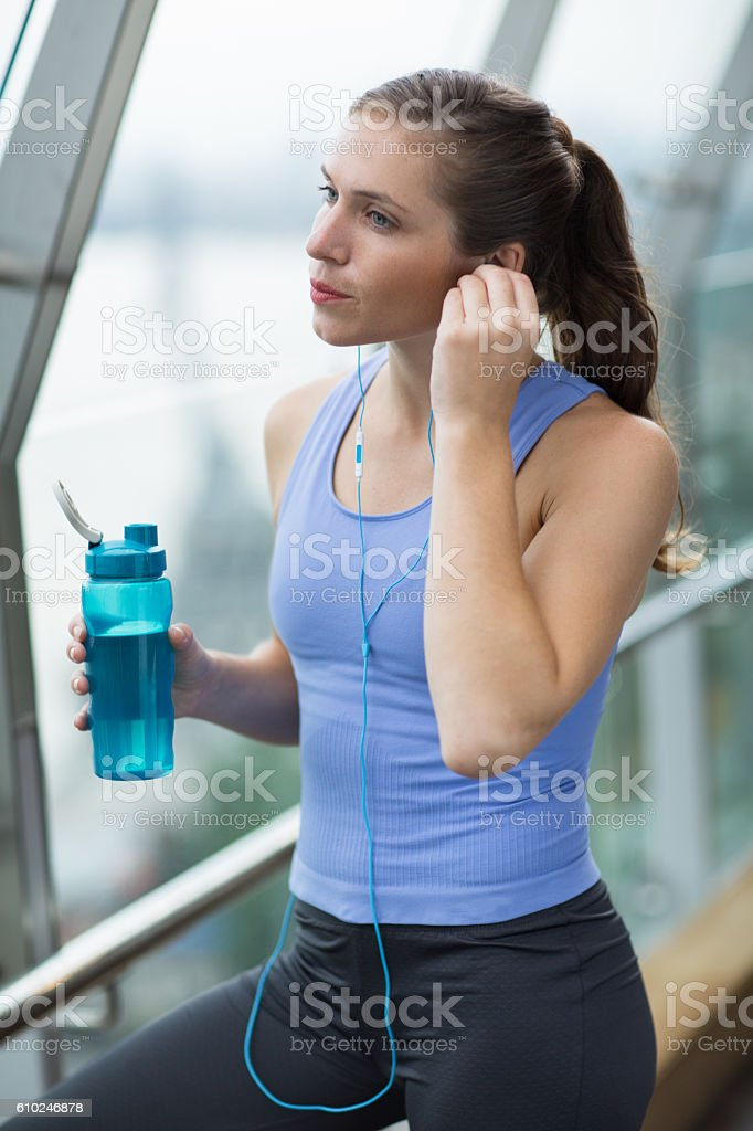 Serious woman listening to music after sports stock photo