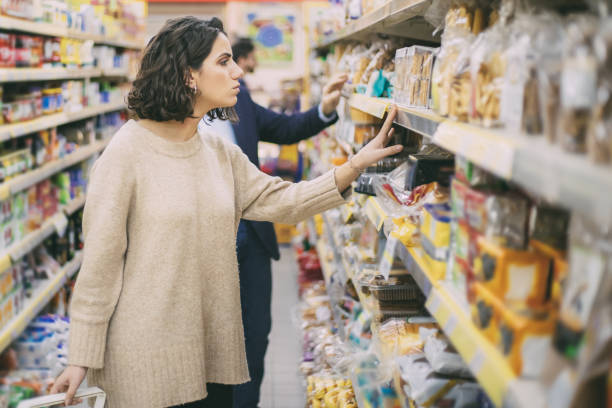 Serious woman looking at cookies in grocery store stock photo
