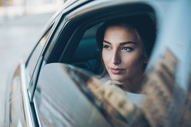 Serious woman looking out of a car window - foto de stock