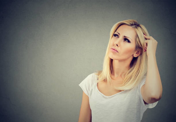 serious woman looking up in contemplation - stupidblonde stock pictures, royalty-free photos & images