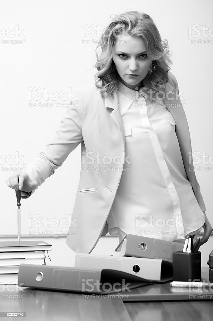 Serious woman near office table stock photo