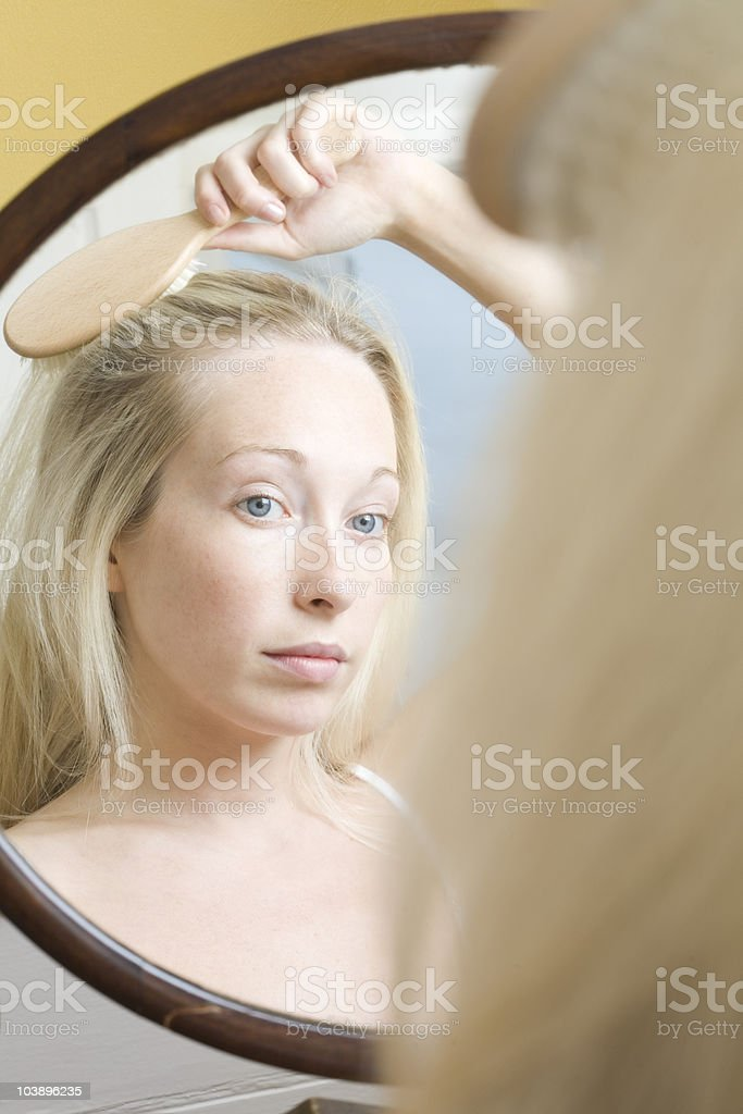 Serious woman peering into mirror looking at her reflection and brushing hair with hairbrush stock photo