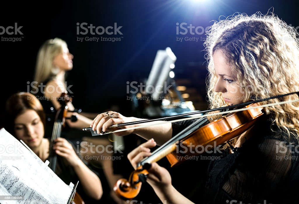 Serious woman playing the violin. stock photo