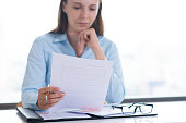 istock Serious woman reading and examining document 1024127182