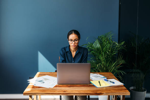 Serious woman sitting at a table and working remotely on a laptop from home stock photo