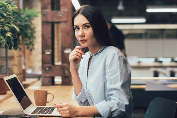 Serious woman sitting with her gadget stock photo stock photo