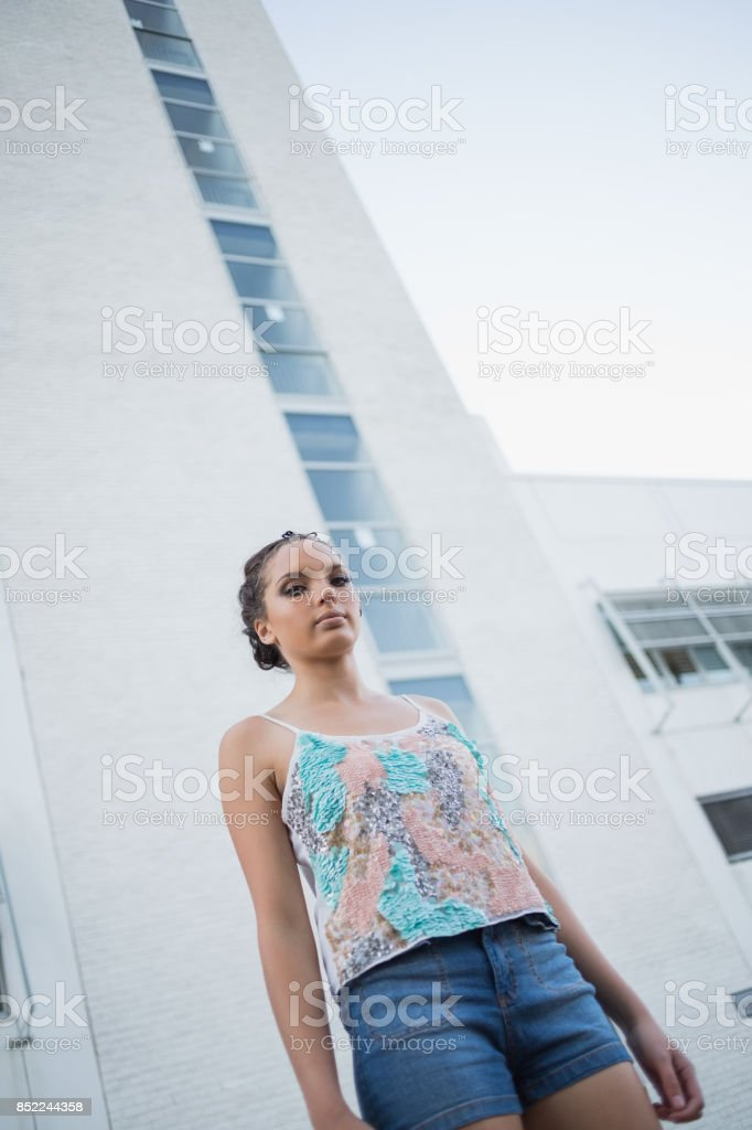 Serious woman standing in front of a huge bulding stock photo