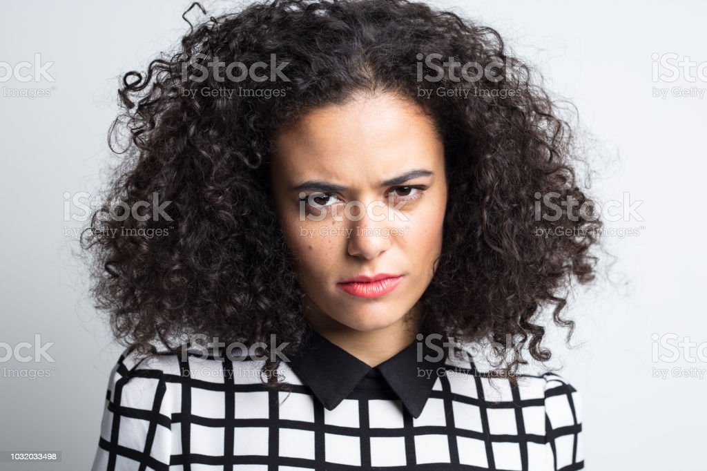 Serious woman staring at camera Close up portrait of serious young woman staring at camera against gray background 20-24 Years Stock Photo