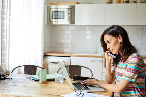 Seriöse Frau, die am Telefon spricht, während sie Laptop benutzt – Foto