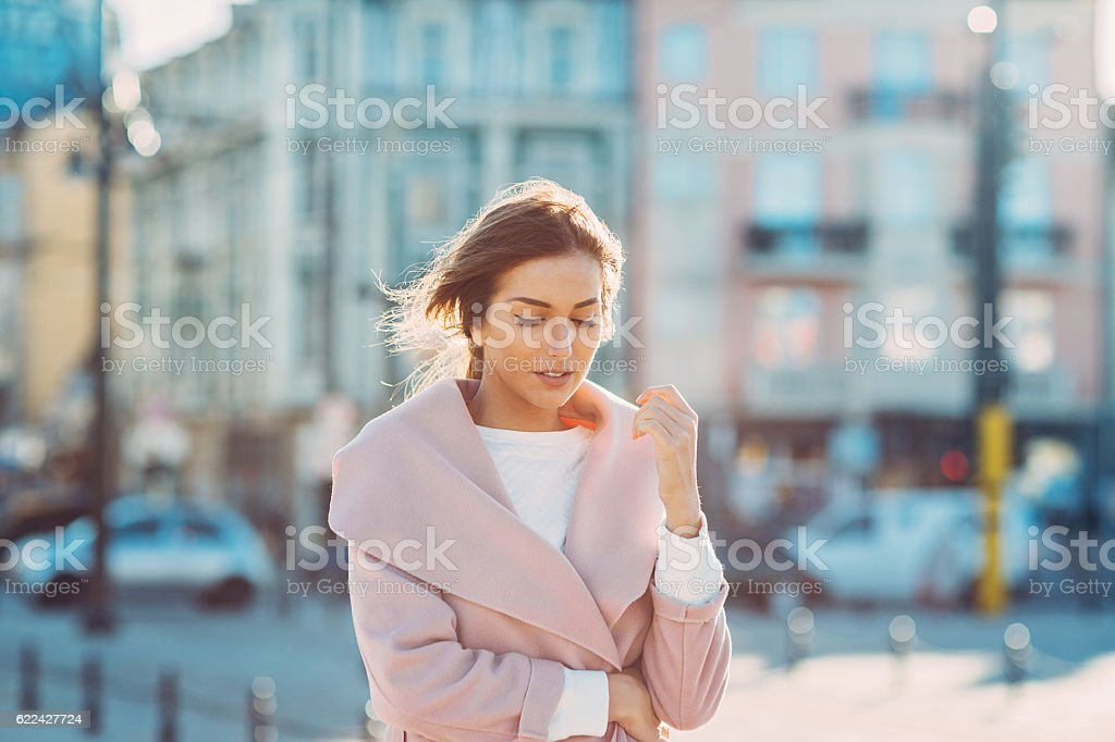 Serious woman walking outdoors on a cold sunny day stock photo