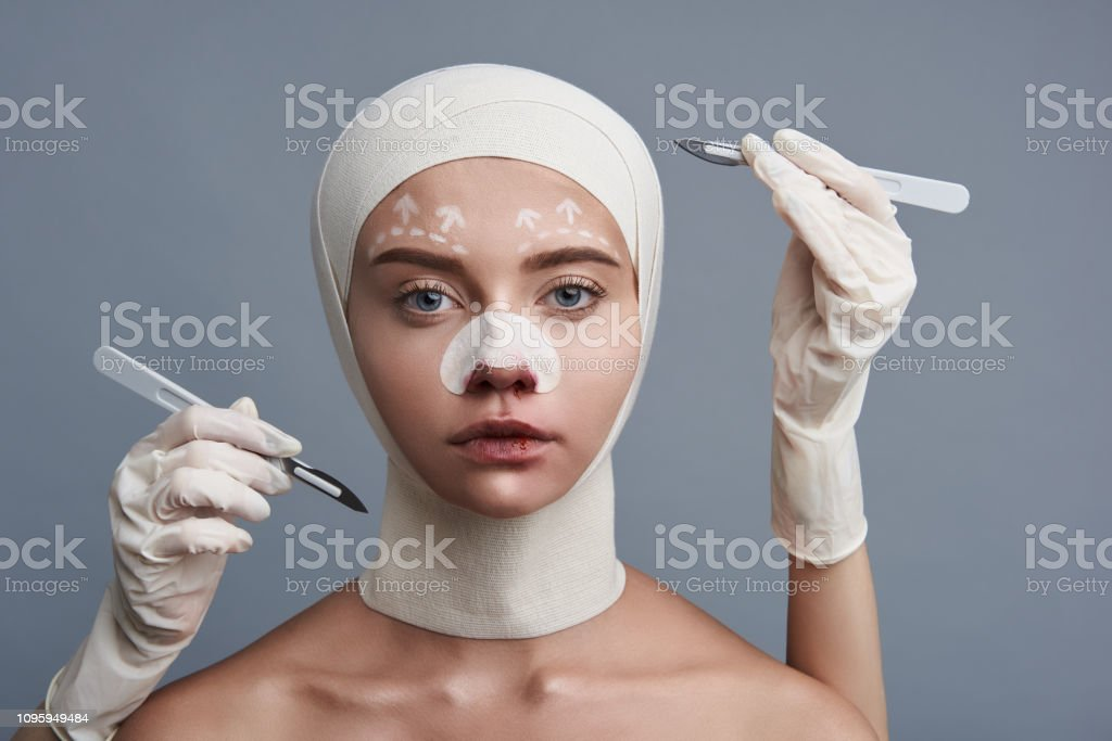 Calm young woman wearing bandages on her head and two scalpels being...