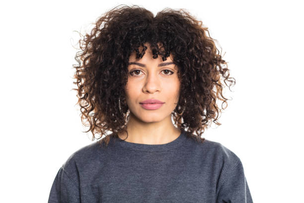 Serious woman with curly hair Portrait of serious young woman with short curly hair staring at camera on white background. Studio shot of female model wearing a t-shirt. curly hair stock pictures, royalty-free photos & images