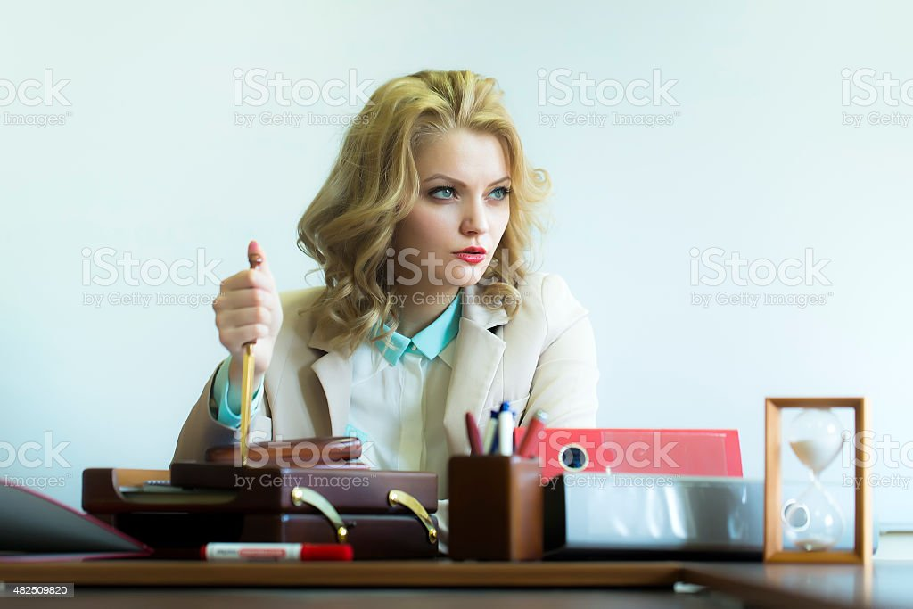 Serious woman with paper knife in office stock photo