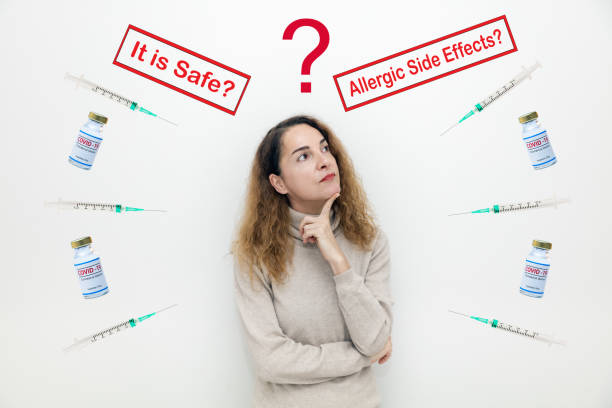 A serious woman with questions and doubts with covid-19 vaccine bottles and It is Safe and Allegic Side Effects signs stock photo