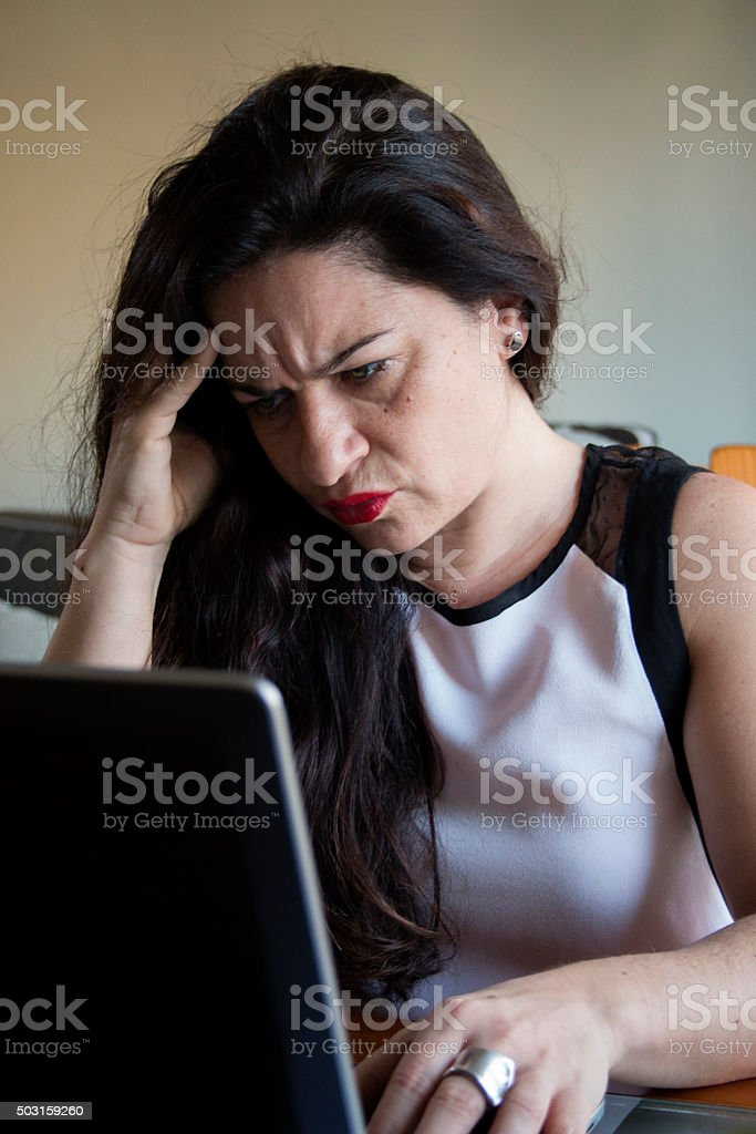 Serious woman working on her laptop at home office desktop stock photo