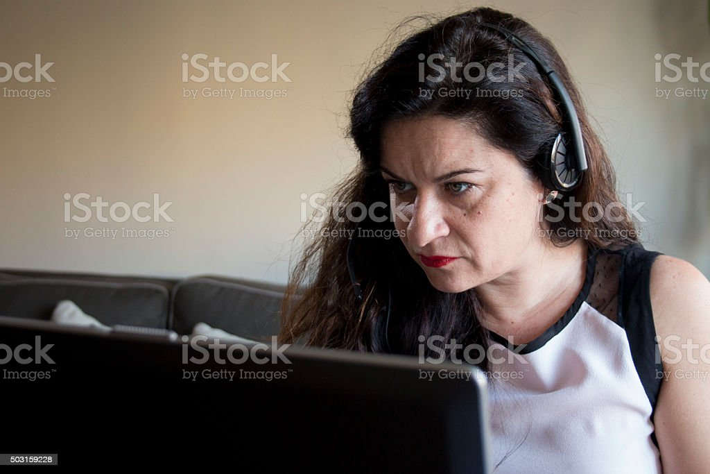 Serious woman working on laptop at home office desktop stock photo
