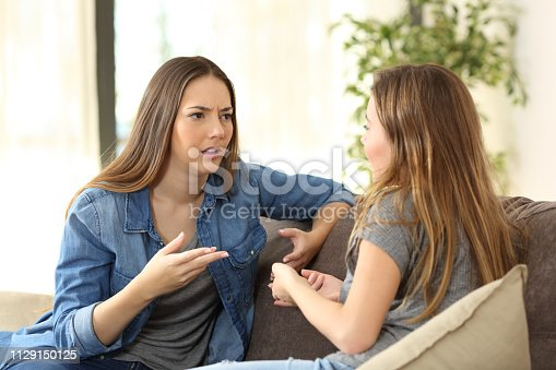 istock Serious women talking on a couch at home 1129150125