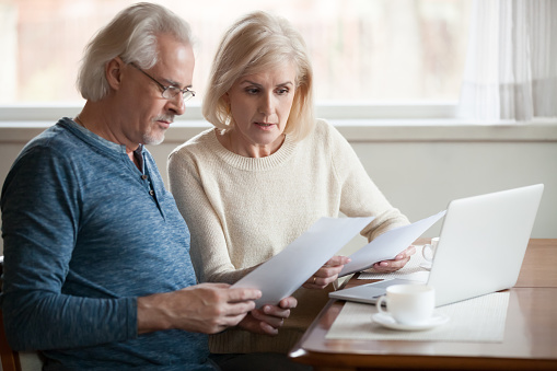 istock Serious worried senior couple reading documents calculating bills to pay 1049512594