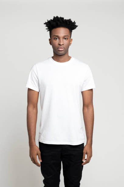 serious young afro american man standing in studio - t shirt stock photos and pictures