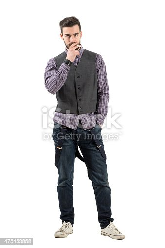 istock Serious young bearded man smoking cigarette looking at camera 475453858