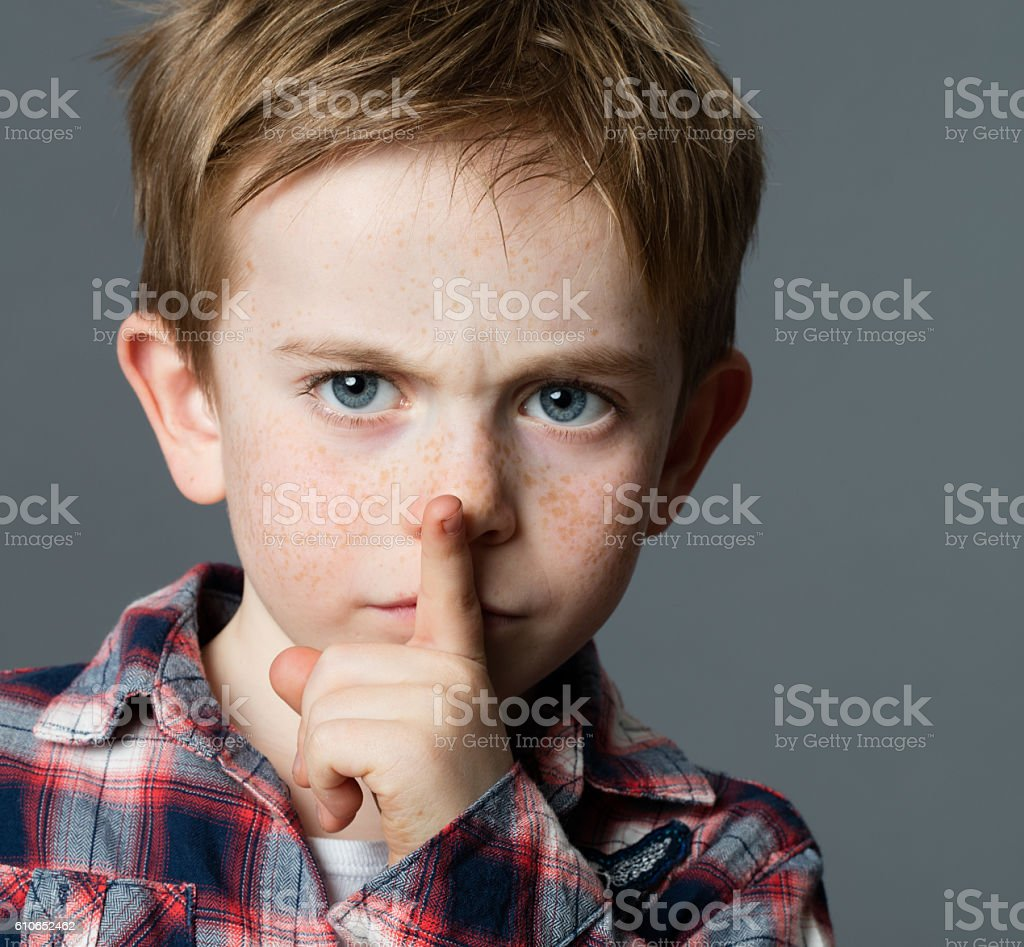 serious young boy asking for silence with finger on lips stock photo