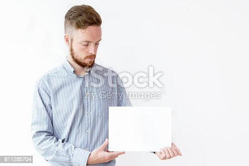 istock Serious young businessman showing blank placard 811285704
