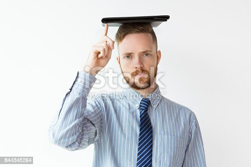 istock Serious young businessman with folder on head 844345264