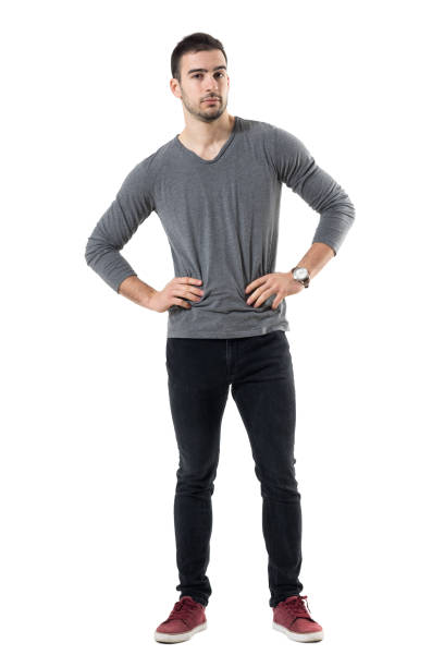Serious young casual man with hands on waist looking at camera. Serious young casual man with hands on waist looking at camera. Full body length portrait isolated over white studio background. akimbo stock pictures, royalty-free photos & images