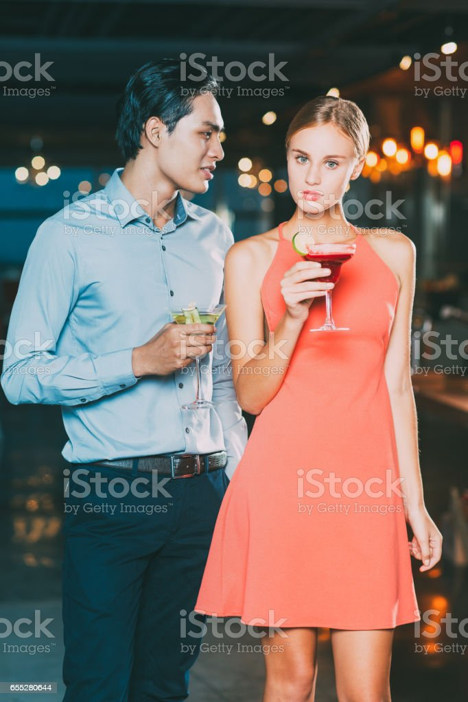 Serious Young Couple With Cocktails At Party Stock Photo & More Pictures of  Adult