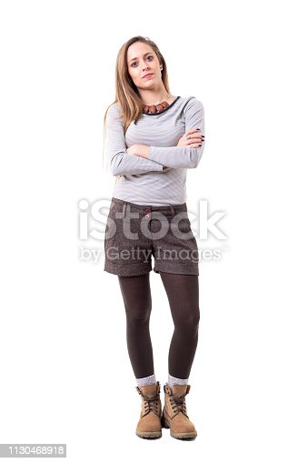Serious young cute woman in second hand hipster style clothes looking at camera with crossed arms. Full body isolated on white background.