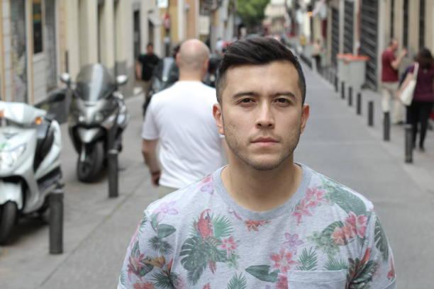 Serious young Eurasian man outdoors stock photo