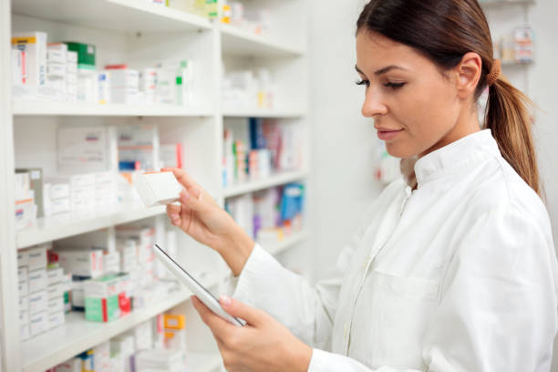Serious young female pharmacist using tablet stock photo