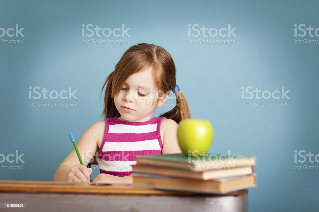 Serious Young Girl Student Sitting at Desk Doing Work royalty-free stock photo