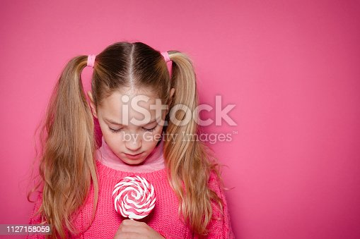 Blonde young girl with pigtails holding and looking down with a serious attitude to a red and white lollipop shot against pink background. The girl is wearing a pink sweater. The composition is at the left leaving useful copy space for text and/or logo at the right. Predominant color is pink. DSRL studio photo taken with Canon EOS 5D Mk II and Canon EF 70-200mm f/2.8L IS II USM Telephoto Zoom Lens