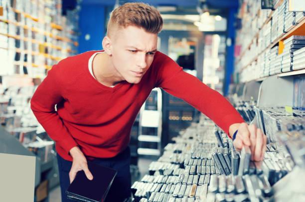 ernsten jungen mann suchen neue cd und dvd im shop - cd ständer stock-fotos und bilder
