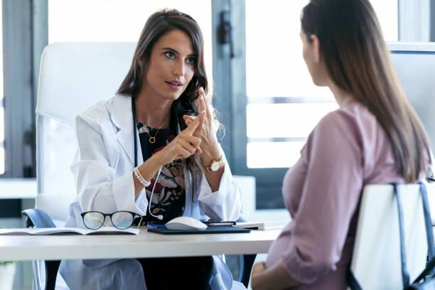 Seriöser junger Gynäkologe gibt Richtlinien für seine schwangere Patientin in der Klinik. – Foto