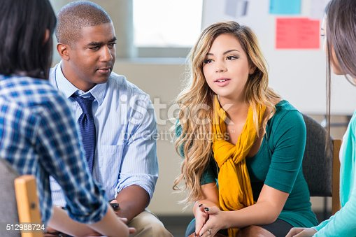 istock Serious young Hispanic woman in group therapy 512988724