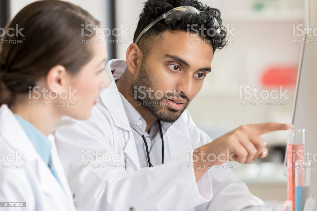 Serious young male lab intern discusses experiment results with coworker stock photo
