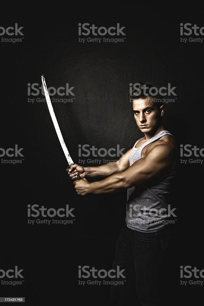 Serious young man and sword royalty-free stock photo