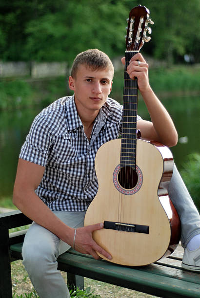 serious young man holding a guitar by the river stock photo
