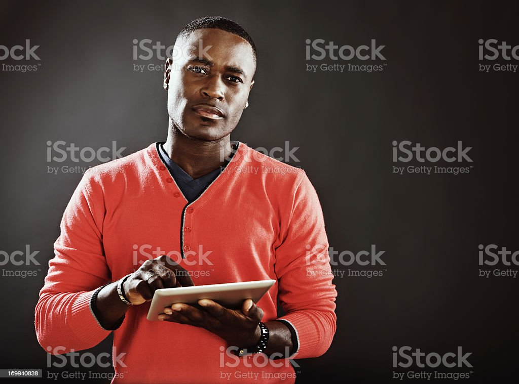 Serious young man holding digital tablet-style computer stock photo