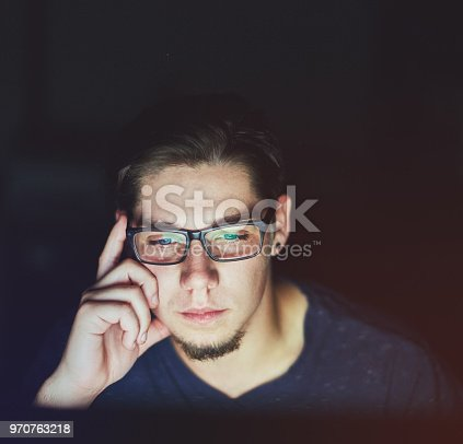 A serious-looking young man in glasses rests his head on his hand as he works late on his computer.