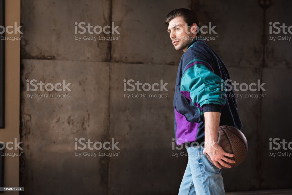 serious young man in vintage windcheater with basketball ball royalty-free stock photo