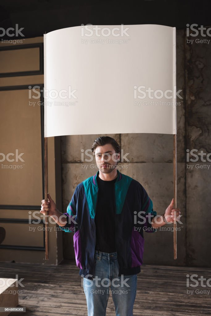 serious young man in vintage windcheater with blank placard royalty-free stock photo
