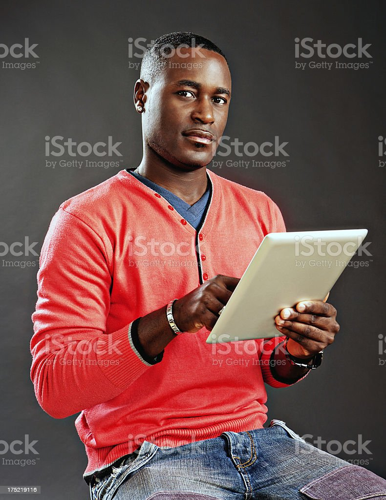 Serious young man looks up from digital tablet he holds stock photo
